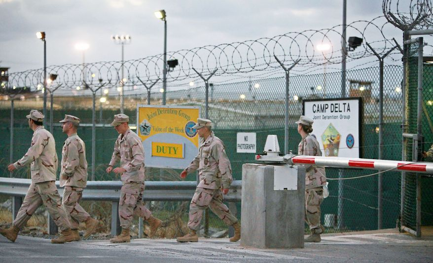 U.S. troops in May 2009 walk near the military detention facility at Guantanamo Bay, Cuba. Congressional Republicans have expressed new suspicions that the Obama administration intends to move Guantanamo detainees to Thomson Correctional Center, a currently unused facility in Illinois. (Associated Press)