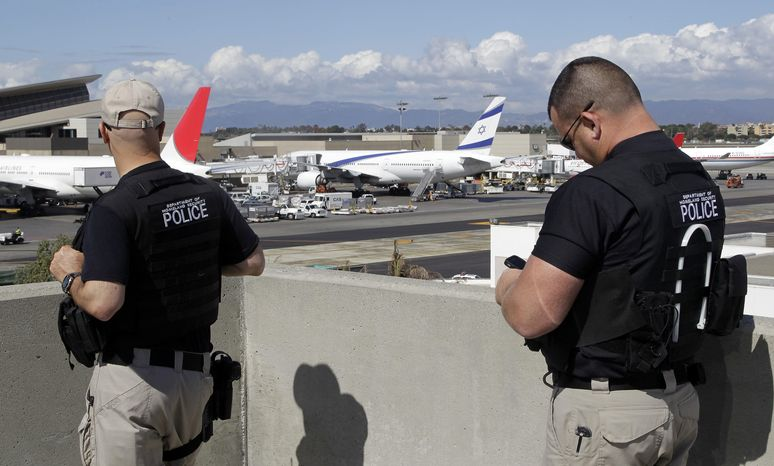 Department of Homeland Security police officers keep an eye on planes at Los Angeles International Airport. (AP Photo/Damian Dovarganes)