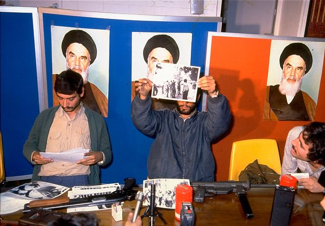 Iranian student spokesmen hold up photos of blindfolded American hostages, during a press conference in Tehran Monday November 5, 1979.  The hostages are members of the staff of the United States Embassy in Tehran, which was stormed by students November 4.  (AP Photo)