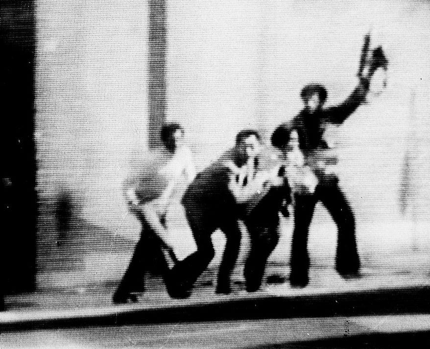 An armed man brandishes his weapon, Feb. 14, 1979, in Teheran, as a couple crouches low during a dash to cross the street near the U.S. Embassy.  Photo was made from video monitor showing ABC-TV.  (AP Photo)