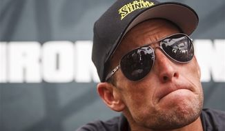 **FILE** Seven-time Tour de France champion Lance Armstrong grimaces during a news conference after the Memorial Hermann Ironman 70.3 Texas triathlon in Galveston, Texas, on April 1, 2012. (Associated Press/Houston Chronicle)