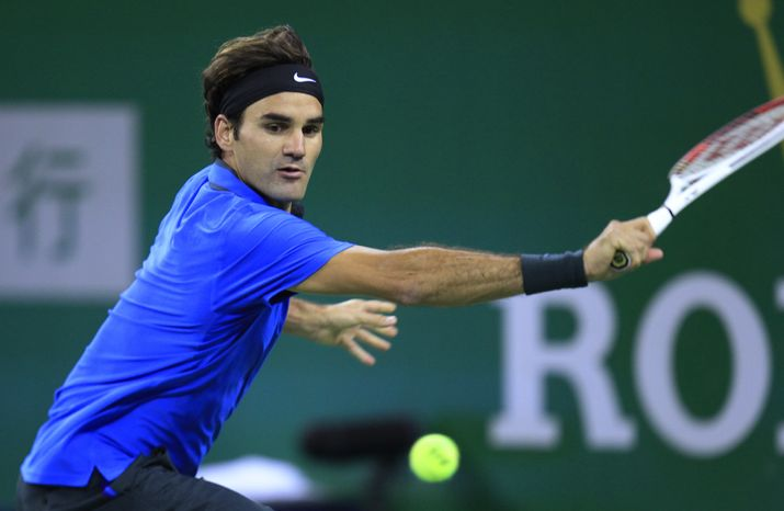 Roger Federer returns the ball against Stanislas Wawrinka during the third round of the Shanghai Masters tennis tournament at Qizhong Forest Sports City Tennis Center in Shanghai, China, on Oct. 11, 2012. Federer won 4-6 7-6(4), 6-0. (Associated Press)