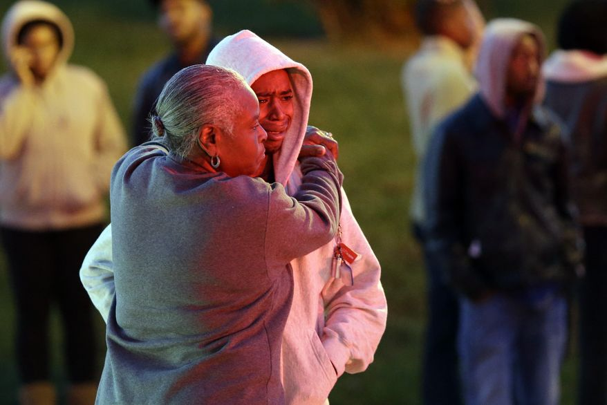 Barbara Hopkins (left) hugs her grandson, whose nickname was given only as Mick, outside her son's house in Baltimore on Thursday, Oct. 11, 2012, where an early morning fire claimed the lives of an adult and four children. (AP Photo/Patrick Semansky)