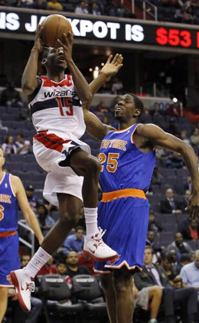 Washington Wizards guard Jordan Crawford (15) goes up for a shot over New York Knicks center Henry Sims (25) during the first quarter of an NBA preseason basketball game in Washington, Thursday, Oct. 11, 2012. The Knicks defeated the Wizards 108-101. (AP Photo/Ann Heisenfelt)