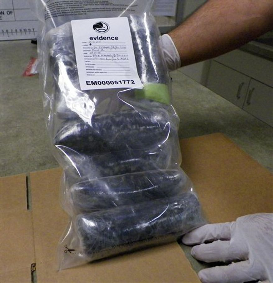 **FILE** A U.S. Drug Enforcement Administration technician holds several pounds of Mexican meth confiscated in the St. Louis area on Sept. 7, 2012. (Associated Press)