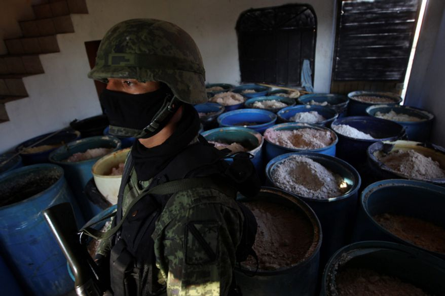 """A soldier stands in a room full of barrels containing white and yellow powder after a seizure of 15 tons of pure methamphetamine at a small ranch in Tlajomulco de Zuniga, on the outskirts of Guadalajara, Mexico, on Sunday, Feb. 9, 2012. Mexican drug cartels are flooding U.S. cities with cheap, extraordinarily pure methamphetamine made in factorylike """"superlabs."""" (AP Photo/Bruno Gonzalez)"""
