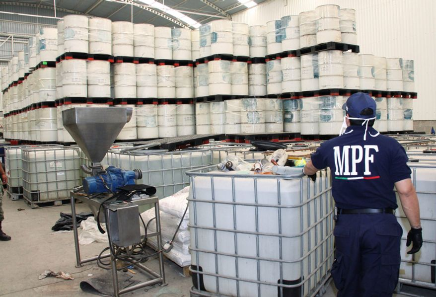 Police from Mexico's Federal Public Ministry looks at drums of precursor chemicals for methamphetamine that were seized in Queretaro, Mexico, on Monday, June 20, 2011. (AP Photo/Mexican Attorney General's Office)