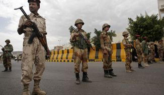 **FILE** Yemeni soldiers stand guard as protesters demonstrate to denounce terror attacks and hail the decisions by Yemen's president Abed Rabbu Mansour Hadi to replace security officials in Sanaa, Yemen. (Associated Press)