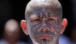 An inmate belonging to the Mara Salvatrucha, or MS-13, gang stands inside a prison in Ciudad Barrios, El Salvador, on March 26, 2012. (Associated Press) ** FILE **