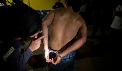 **FILE** A police officer inspects tattoos on Mara Salvatrucha gang member Jose Alexander Carranza after his arrest in San Pedro Sula, Honduras, on March 8, 2012. (Associated Press)