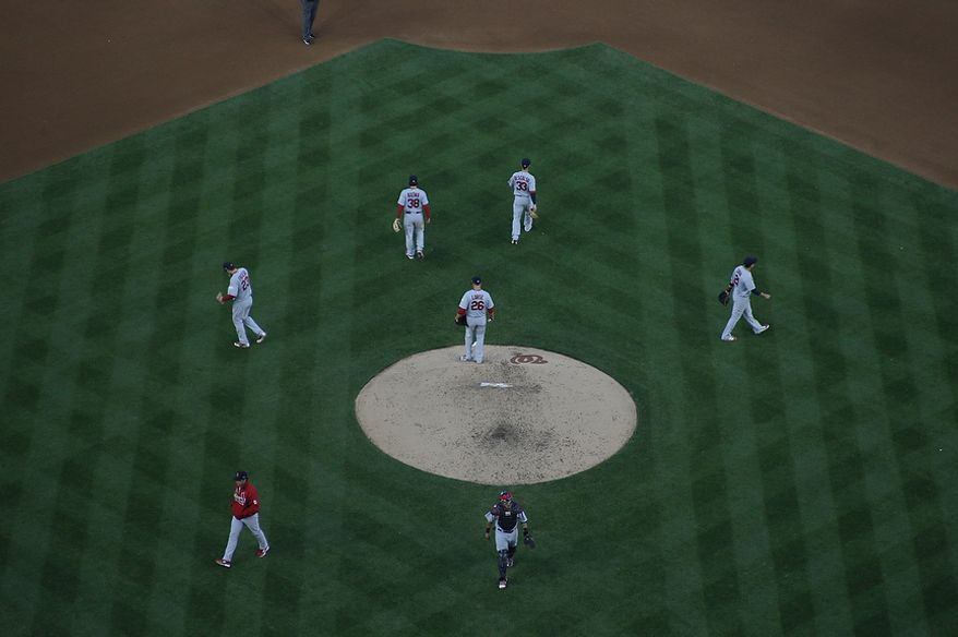 Cardinals players disperse after meeting on the mound with starting pitcher Kyle Lohse (26) during Game 4 of the National League Division Series between the Washington Nationals and the St. Louis Cardinals at Nationals Park, Thursday, October 11, 2012. (Craig Bisacre/The Washington Times)