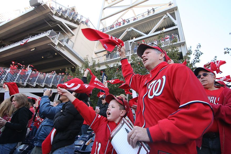 Erik Sullivan and his son, Timmy Sullivan, 8, of Arlington, Va., wave their rally towels during the first inning of Game 4 of the National League Division Series between the Washington Nationals and the St. Louis Cardinals at Nationals Park, Thursday, October 11, 2012. (Craig Bisacre/The Washington Times)