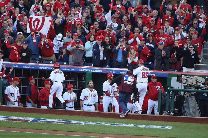Fans go wild as Nationals first baseman Adam LaRoche (25) is congratulated by teammates after his solo home-run in the bottom of the second inning to give the Nats a 1-0 lead inGame 4 of the National League Division Series between the Washington Nationals and the St. Louis Cardinals at Nationals Park, Thursday, October 11, 2012. (Craig Bisacre/The Washington Times)