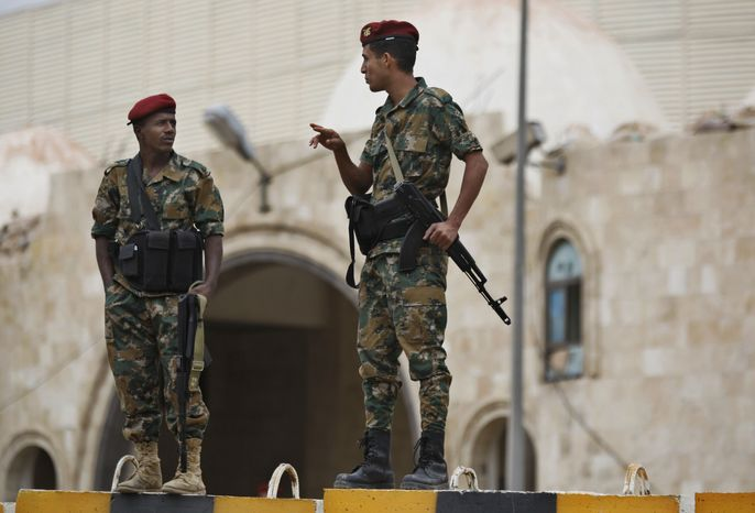 ** FILE ** Yemeni soldiers stand guard in front of Yemen's President Abed Rabbu Mansour Hadi's house as protestors demonstrate to denounce terror attacks and hail the decisions by Hadi to replace security officials in Sanaa, Yemen, Wednesday, Sept. 12, 2012. (AP Photo/Hani Mohammed)