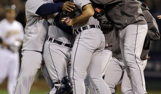 Detroit Tigers teammates hug pitcher Justin Verlander, center, after the Tigers beat the Oakland Athletics 6-0 in Game 5 of an American League division baseball series in Oakland, Calif., Thursday, Oct. 11, 2012.(AP Photo/Marcio Jose Sanchez)
