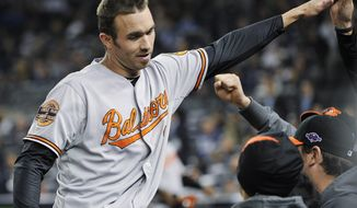 Baltimore Orioles' J.J. Hardy celebrates with teammates after driving in a run during the 13th inning of Game 4 of the American League division baseball series against the New York Yankees Thursday, Oct. 11, 2012, in New York. The Orioles won 2-1. (AP Photo/Bill Kostroun)
