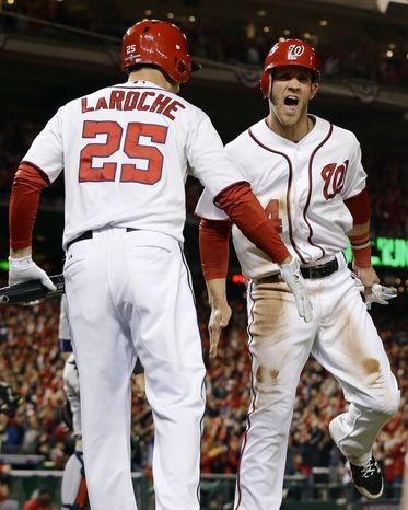 Washington Nationals' Bryce Harper, right, low-fives Adam LaRoche after scoring on a home run by Ryan Zimmerman in the first inning of Game 5 of the National League division baseball series against the St. Louis Cardinals on Friday, Oct. 12, 2012, in Washington. (AP Photo/Alex Brandon)