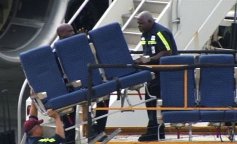 "In this photo provided by WBZ-TV seats from an American Airlines 757 are carried before receiving ""Main Cabin Extra Refurbishment"" Tuesday, Oct. 2, 2012, at Logan International Airport in Boston. American Airlines says passenger seats on a third flight came loose as the plane was airborne Tuesday, and it's continuing to inspect other jets with similar seating. The airline acknowle"