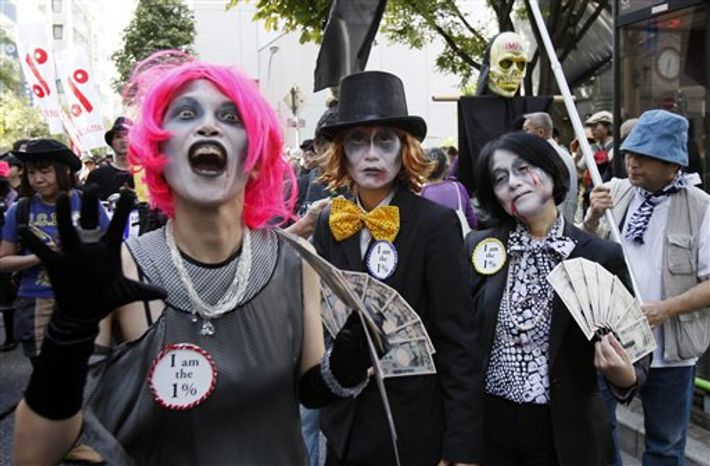 Participants march during a demonstration against the annual meetings of the IMF and World Bank being held in Tokyo, Saturday, Oct. 13, 2012. (AP Photo/Koji Sasahara)