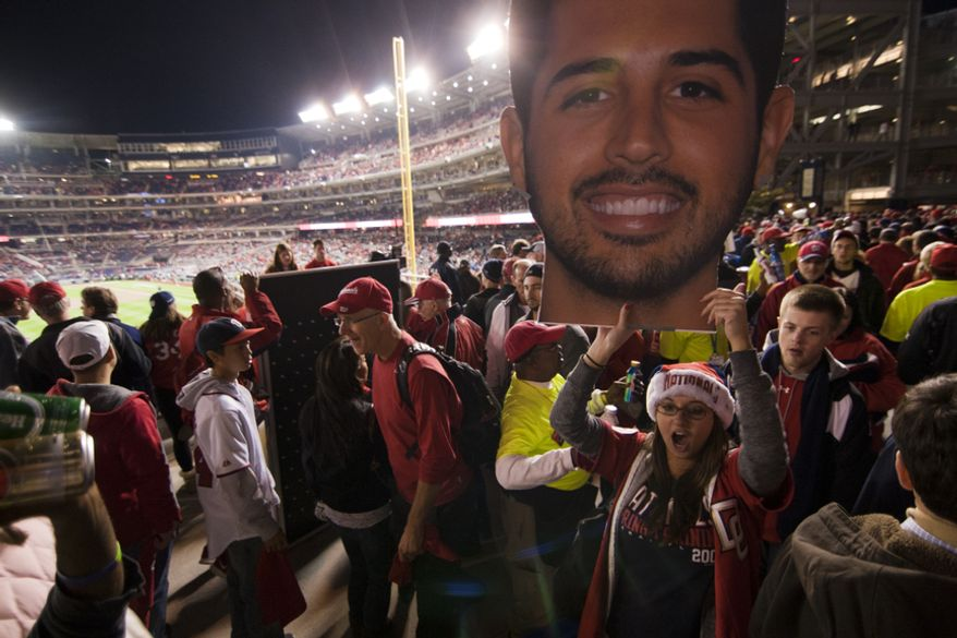 A fan walks though centerfield plaza with an enlarged poster head of starting Nats pitcher Gio Gonzalez before Gamee 5 of the National League Division Series between the Washington Nationals and the St. Louis Cardinals at Nationals Park, Thursday, October 11, 2012. (Craig Bisacre/The Washington Times)