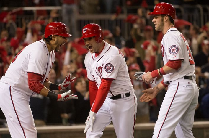 Washington Nationals shortstop Ian Desmond (20), left, celebrates as Washington Nationals third baseman Ryan Zimmerman (11) hits a two run homer to bring Washington Nationals center fielder Bryce Harper (34), right, home in the first inning to put the Washington Nationals up 3-0  against the St. Louis Cardin