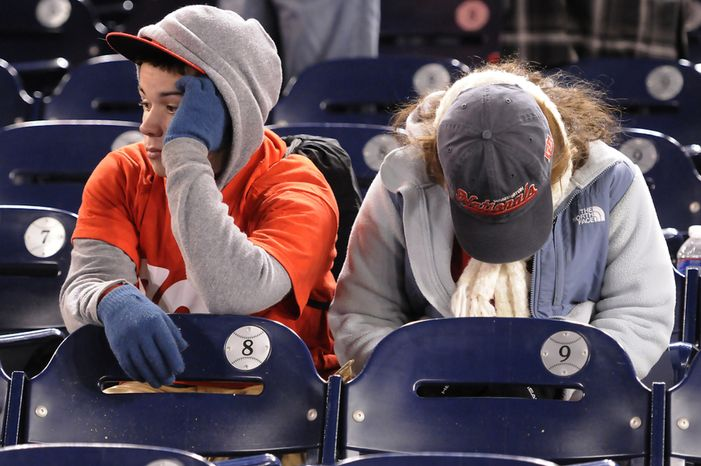 (L to R) Paul Hefner, 16, and Isabel Hefner, 18, from Great Falls, Va., sit dejected in the stands after the Washington Nationals loss to the St. Louis Cardinals 9-7 in Game 5 of the National League Division Series at Nationals Park, Friday, October 12, 2012. (Preston Keres/Special to The Washington Times)