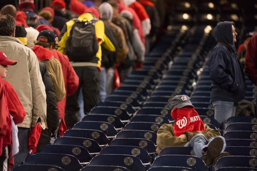 A fan covers his face as the Washington Nationals lose to the St. Louis Cardinals 9-7 in game five of the National League Division Series at Nationals Park, Washington, D.C., Saturday, October 13, 2012. (Andrew Harnik/The Washington Times)