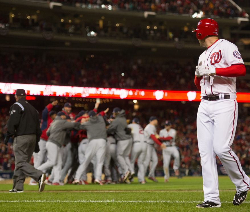 Washington Nationals third baseman Ryan Zimmerman (11), right, walks off the field as the St. Louis Cardinals celebrate their win over the Washington Nationals in game five of the National League Division Series at Nationals Park, Washington, D.C., Saturday, October 13, 2012. (Andrew Harnik/The Washington Times)