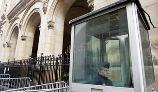 A police officer sits in a guard post outside a Paris synagogue. Recent attacks have unsettled Jews, many of whom thought that anti-Semitism had faded. (The Associated Press)