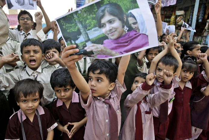 A Pakistani boy holds up a picture of 14-year-old schoolgirl Malala Yousufzai, who was shot on Tuesday, Oct. 9, 2012, by the Taliban for speaking out in support of education for women. The schoolboy and ot