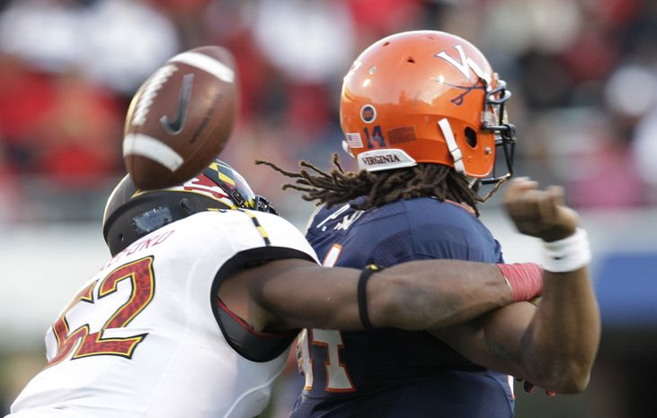 Maryland linebacker Darin Drakeford (52) forces a fumble from Virginia quarterback Phillip Sims (14) during the second half of an NCAA college football game at Scott Stadium in Charlottesville, Va., on Saturday, Oct. 13, 2012. Maryland won the game 27-20. (AP Photo/Steve Helber)