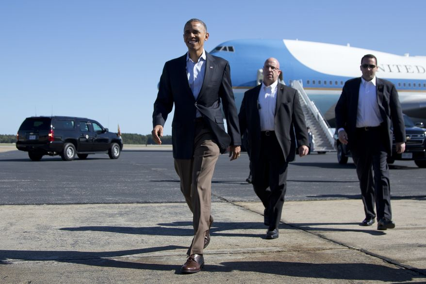 President Obama walks to greet people on the apron as he arrives at Newport News/Williamsburg International Airport aboard Air Force One on Saturday, Oct. 13, 2012, in Williamsburg, Va. (AP Photo/Carolyn Kaster)