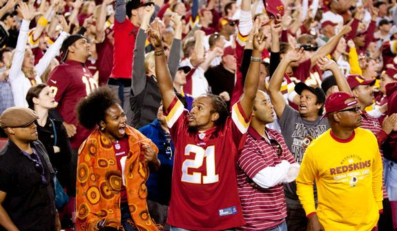 Fans react to Washington Redskins quarterback Robert Griffin III (10) 76 yard touchdown in the forth quarter against the Minnesota Vikings.  (Craig Bisacre/The Washington Times)