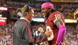 Washington Redskins quarterback Robert Griffin III (10) laughs with Washington Redskins head coach Mike Shanahan on the sideline after running a 76 yards for a touchdown to put the Washington Redskins up 38-26 in the fourth quarter. (Craig Bisacre/ The Washington Times)