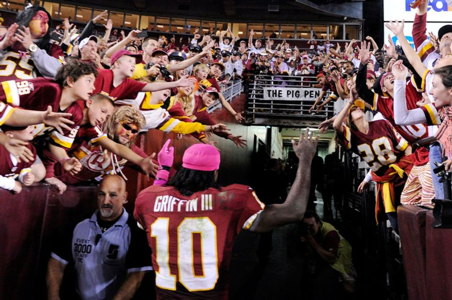 Washington Redskins quarterback Robert Griffin III (10) leaves the field after providing the Redskins their first home victory in nine games in Landover, Md., Sunday, October 14, 2012.. (Preston Keres/Special to The Washington Times)