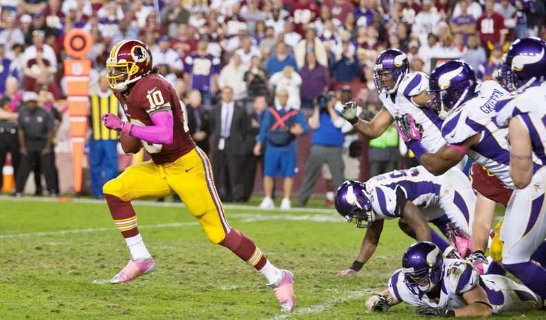 Washington Redskins quarterback Robert Griffin III (10) breaks though tacklers for a 76 yard touchdown in the forth quarter against the Minne
