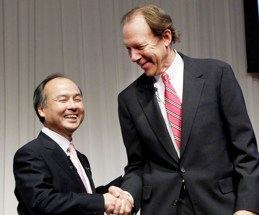 Softbank Corp. President Masayoshi Son (left) and Sprint Nextel Corp. Chief Executive Dan Hesse shake hands Monday after a deal was reached for Softbank to acquire 70 percent of Sprint for $20.1 billion in the largest ever foreign acquisition by a Japanese company. (Associated Press)