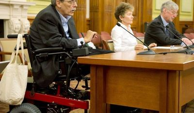 Kelly Buckland (left), of the National Council on Independent Living, at a Monday hearing at D.C. city hall, discusses the Accessible Parking Amendment Act of 2012, which would designate 1,800 parking spaces with red-top meters for the disabled. (Barbara L. Salisbury/The Washington Times)