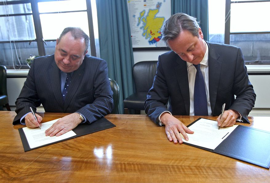 British Prime Minister David Cameron (right) and Scottish First Minister Alex Salmond sign a referendum agreement on Scottish independence during a meeting at St Andrew's House in Edinburgh, Scotland, on Monday, Oct. 15, 2012. (AP Photo/Gordon Terris, Pool)