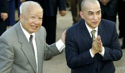 ** FILE ** Cambodia's King Norodom Sihanouk (left) introduces his son and successor, King Norodom Sihamoni, upon their arrival at Phnom Penh airport in Cambodia in 2004. (AP Photo/Andy Eames)