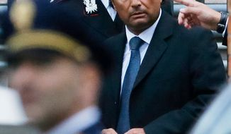 ** FILE ** Francesco Schettino (right), the former captain of the cruise ship Costa Concordia, leaves the Teatro Moderno theater where the first hearing of the trial for the Jan. 13, 2012, shipwreck which left 32 people dead, is taking place, in Grosseto, Italy, on Monday, Oct. 15, 2012. (AP Photo/Gregorio Borgia)
