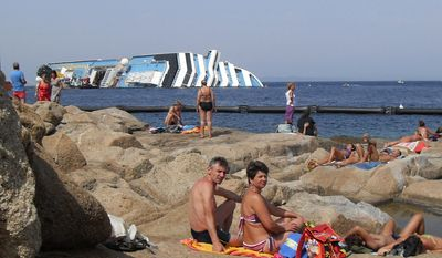 In this image taken Saturday, Aug. 11, 2012, sunbathers sit in front of the wreck of Costa Concordia outside the port of Isola del Giglio in Tuscany, Italy. (AP Photo, Giacomo Aprili)