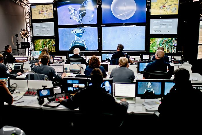 In this photo provided by Red Bull, crew members at the mission control watch the jump of pilot Felix Baumgartner of Austria in Roswell, N.M., on Oct. 14, 2012. Baumgartner came down safely in the eastern New Mexico desert minutes about nine minutes after jumping from his capsule 128,097 feet, or roughly 24 miles, above Earth. (Associated Press/Red Bull Stratos, Joerg Mitter)