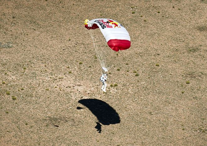 In this photo provided by Red Bull, pilot Felix Baumgartner of Austria lands in the desert after his successful jump on Oct. 14, 2012 in Roswell, N.M. Baumgartner came down safely in the eastern New Mexico desert minutes about nine minutes after jumping from his capsule 128,097 feet, or roughly 24 miles, above Earth. (Associated Press/Red Bull Stratos)