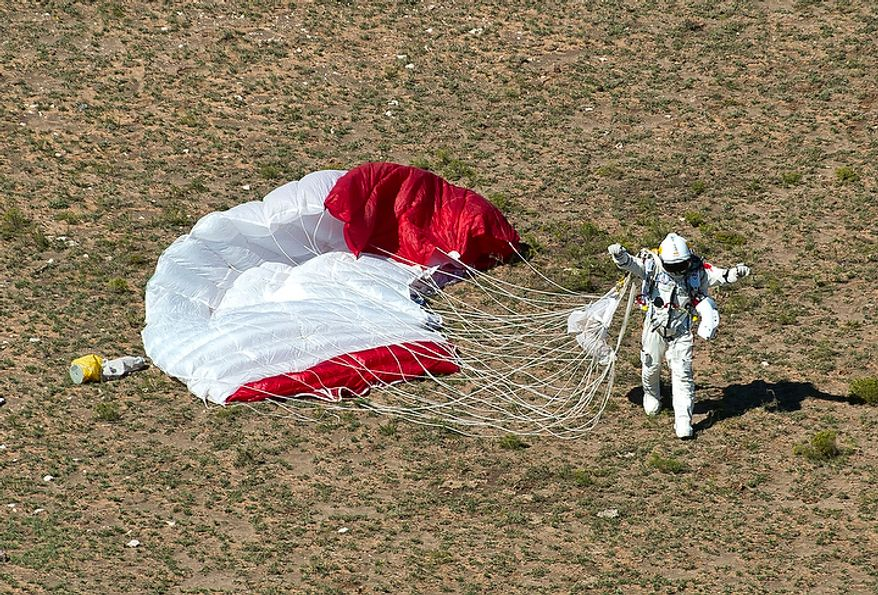 In this photo provided by Red Bull, pilot Felix Baumgartner of Austria celebrates after his successful jump on Oct. 14, 2012 in Roswell, N.M. Baumgartner came down safely in the eastern New Mexico desert minutes about nine minutes after jumping from his capsule 128,097 feet, or roughly 24 miles, above Earth. (Associated Press/Red Bull Stratos, Predrag Vuckovic)