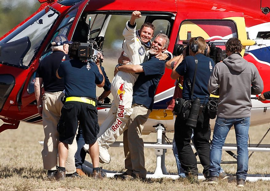 Felix Baumgartner (third from left), of Austria, gets a hug from Mission Control technical project director Art Thompson on Oct. 14, 2012, as television crews and pool photographers converge on the scene after Baumgartner successfully jumped from a space capsule lifted by a helium balloon at a height of just over 128,000 feet above the Earth's surface in Roswell, N.M. (Associated Press)
