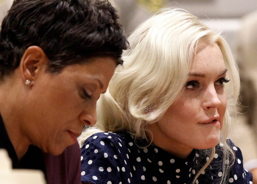 Actress Lindsay Lohan (right) bites her lip as she appears with her attorney, Shawn Chapman Holley, at a probation hearing in Los Angeles Superior Court on Wednesday, Nov. 2, 2011. Superior Court Judge Stephanie Sautner sentenced Miss Lohan on Wednesday to 30 days in jail and warned the actress there would be plenty more time behind bars if she violated further court orders. (AP Photo/Mario Anzuoni, Pool)