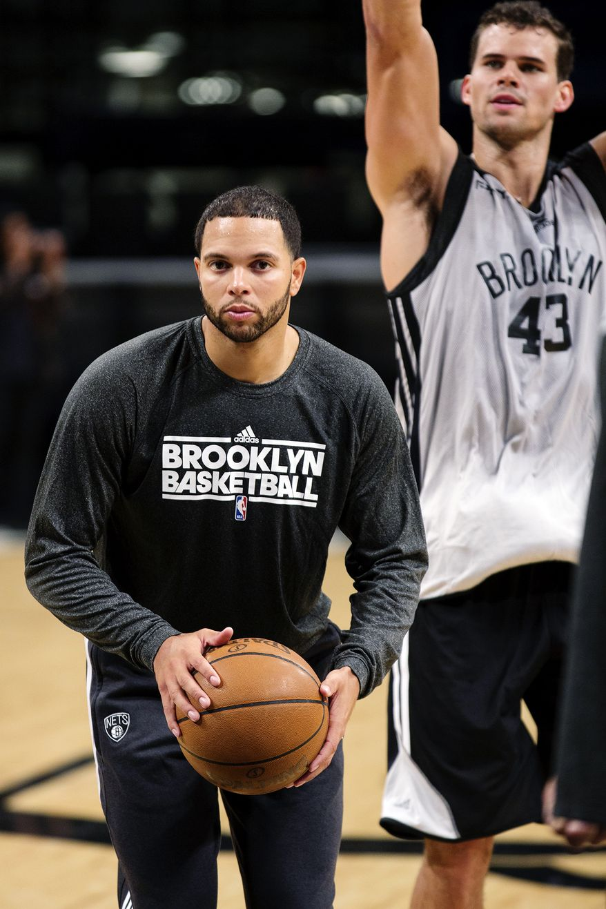 Brooklyn Nets' Deron Williams, left, prepares to shoot during NBA basketball practice at the Barclays Center, Sunday, Oct. 7, 2012, in New York. At right is Kris Humphries. (AP Photo/Craig Ruttle)