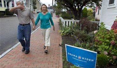 Joe Galli jokingly covers his face while walking with his wife, Thyra, by an Obama/Biden sign in front of a neighbor's home, Friday, Oct. 5, 2012, in Portsmouth, N.H. (AP Photo/Robert F. Bukaty)