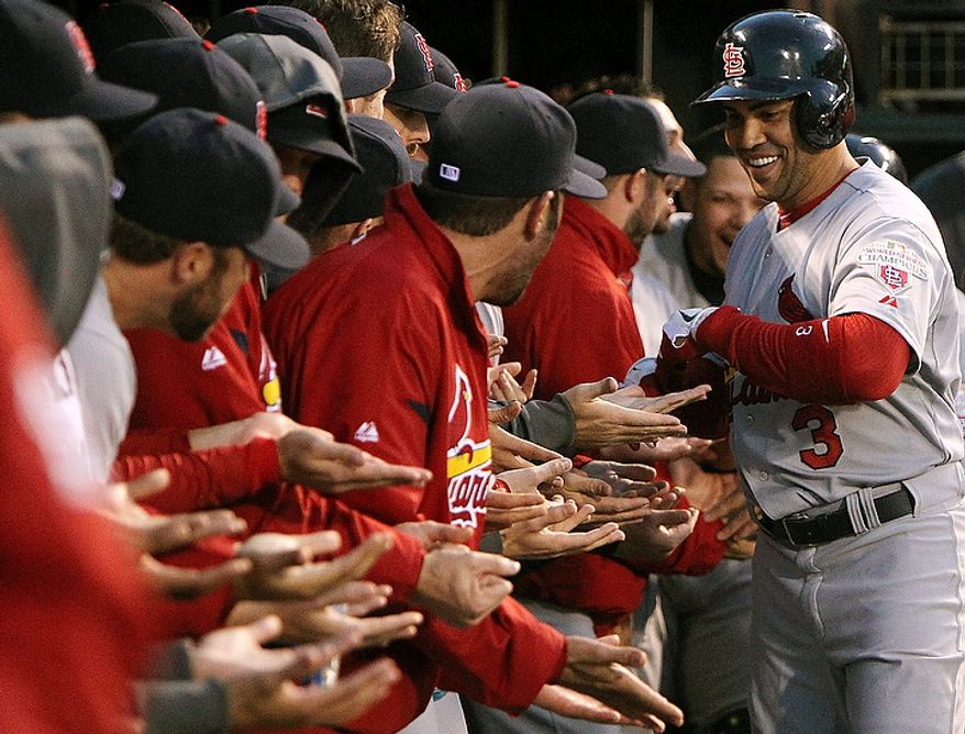St. Louis Cardinals' Carlos Beltran is congratulated by teammates in the dugout after hitting a two-run home run during the fourth inning in Game 1 of baseball's National League championship series against the San Francisco Giants on Sunday, Oct. 14, 2012, in San Francisco. The Cardinals won 6-4. (AP Photo/St. Louis Post-Dispatch, Chris Lee)